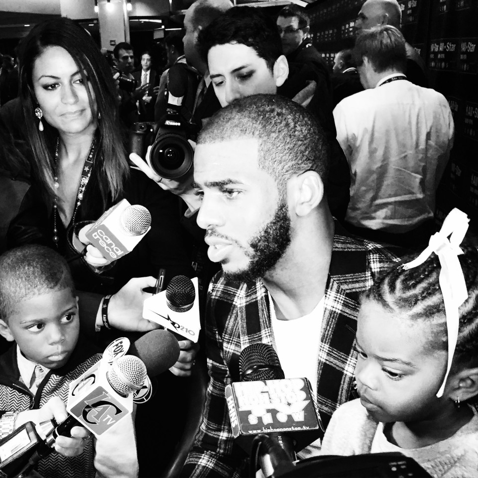 Chris Paul addressing the media with his children on his lap.